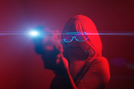Girl with blaster in the futuristic battle. Concept virtual reality, cyber game. Stock Photo