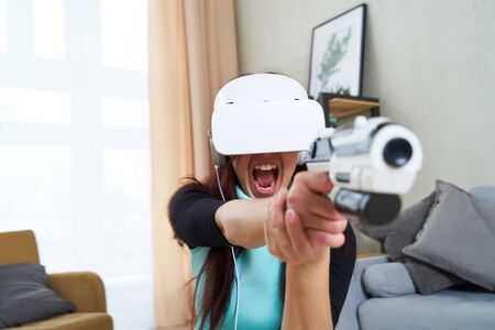Woman with virtual reality headset and blaster is playing game.