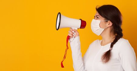 Woman in medical mask with megaphone. Concept of importance of information, warnings people about pandemic.
