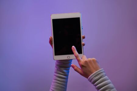 Close-up of mans hands with smartphone and blank black screen on blank purple background. Imagens