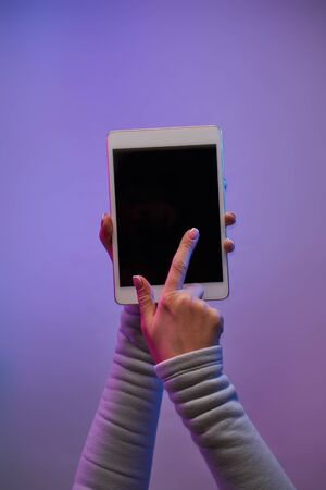 Close-up of man's hands with smartphone and blank black screen on blank purple background. Place for text