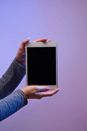 Close-up of mans hands with smartphone and black screen on purple background Imagens