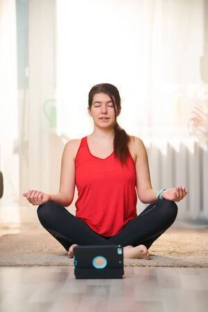 Woman practices yoga and meditates in the lotus position at home using video tutorials.