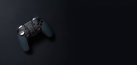 Black gamepad on black background. Gamer concept.