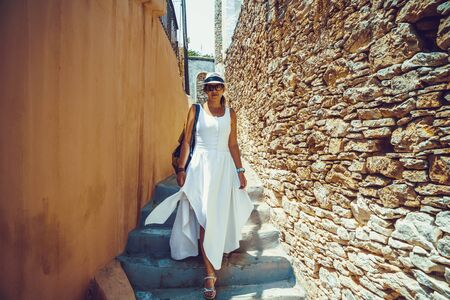 Happy woman traveler is walking and exploring Greek island of Symi, Dodecanese, Greece