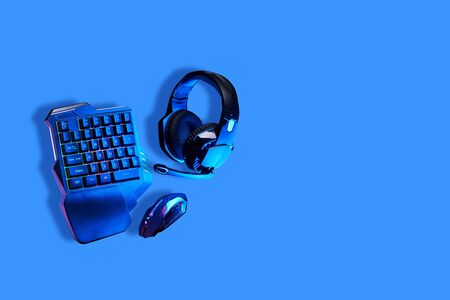 Games keyboard, mouse and headset on blue background.