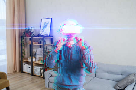 Man with virtual reality headset is playing game and fighting. Image with glitch effect.