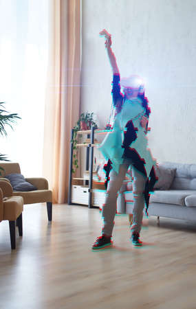 Woman with virtual reality headset rejoices in victory in the game. Image with a glitch effect.