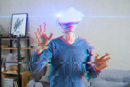 Man is using virtual reality headset. Image with glitch effect. Concept of virtual reality, simulation, gaming and future technology.