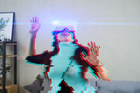 Woman is using virtual reality headset. Image with glitch effect. Concept of virtual reality, simulation, gaming and future technology. Standard-Bild