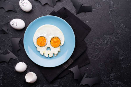 Fried eggs in the shape of a skull. Halloween breakfast.