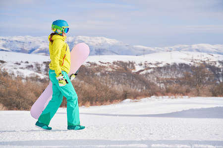 Woman with snowboard against background of mountains