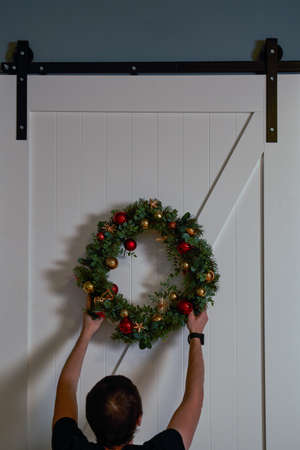 Man decorates the door with a wreath for the holiday of Christmas