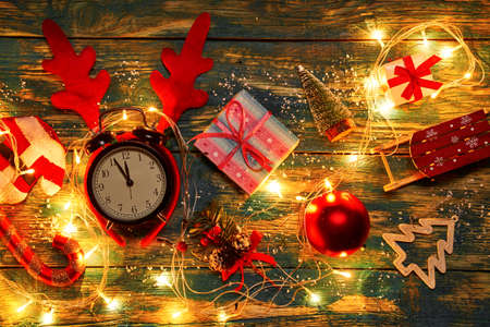 Christmas decorations and clocks showing five to twelve with burning garland Reklamní fotografie