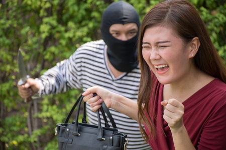 Armed robber and victim with a handbagAsian woman ran to escape the bandits ,criminal concept