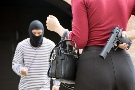 Male robber standing and looking at young woman and young woman hide gun in his back/self-defense of woman,criminal concept