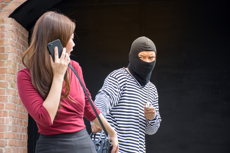 criminal: Male robber robbing a handbag threatening with knife to scared Asian woman in red dress,criminal concept
