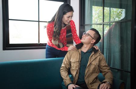 Aantrekkelijke glimlachende vrouw die zich met haar echtgenoot bevindt die omhoog veel liefs kijkt in zijn ogen aangezien zij zich voor een venster bevinden