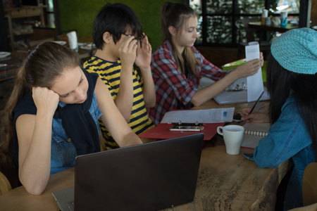 Group of teenage friends working and meeting in team with reports and laptop on wooden tableSelective focus Bored girl Stock Photo