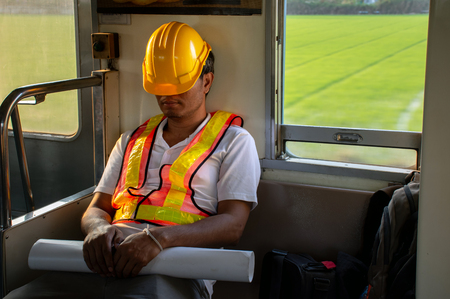 Picture of Asian engineer wearing safety helmet tired fall asleep during working hours in trainEngineer concept