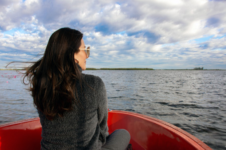 Back view of the young Asian woman enjoy on the boat and looking forward into lagoon