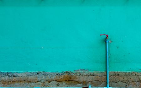 The brick wall is painted green and a faucet start damage. Stock Photo