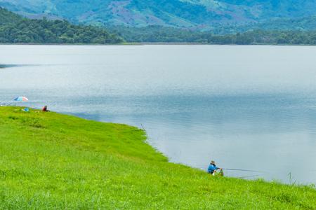Fishermen sit fishing at the Huai Pa Daeng Reservoir , Phetchabun in  Thailand.