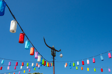 Light poles and lamp with colorful paper on a bright blue sky.