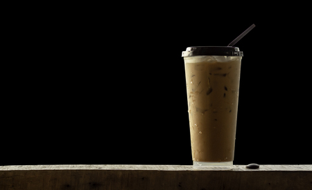 Iced coffee in a plastic glass on wooden , black background.