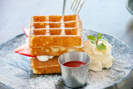 Waffle Strawerry fresh cream in the black plate on wooden table.