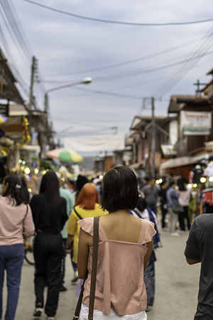 Woman on the street and blurry tourists at Walking Street Chiang Khan, Loei in Thailand. 版權商用圖片