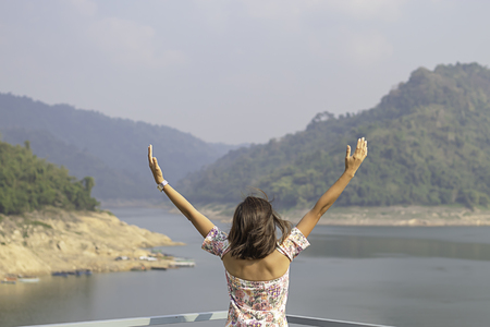 Women raise their arms Background mountains and water at Khun Dan Prakan Chon Dam ,Nakhon Nayok in Thailand.