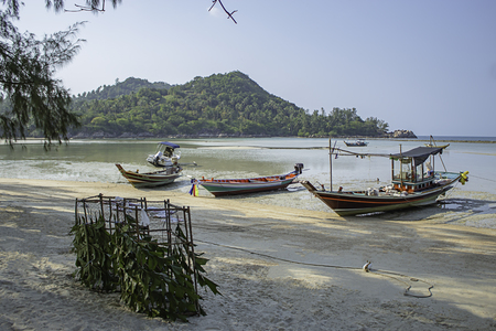 Fishing boats parked on the Beach at Koh Phangan, Surat Thani in Thailand. Stock Photo - 119488010