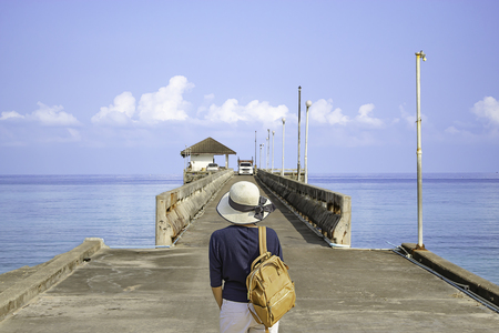 Women shoulder backpack and Wear a hat on the concrete bridge pier fishing in the sea and the bright sky