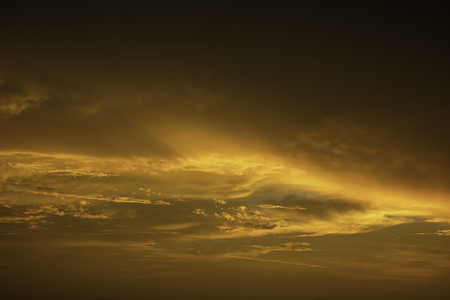 The golden light of the sun and clouds in the sky. Imagens
