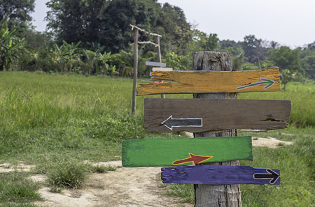 Wooden painted signs on poles Background fields and trees. Imagens