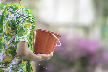 Hand holding Plastic bucket play Songkran festival or Thai new year in Thailand. Stockfoto