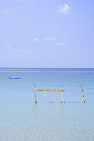 Swing chairs made from wood and fishing boats in the sea Background sky and cloud at Koh Kood, Trat in Thailand.