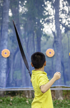 Asian boys are archery in camp adventure. Imagens