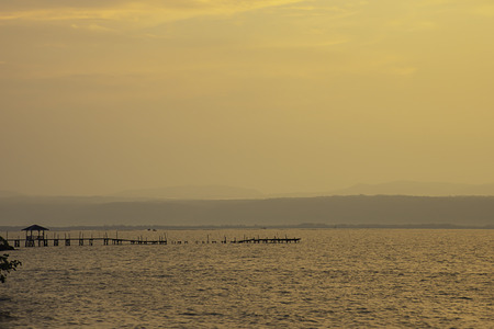 Golden light of sunrise behind the mountains in the sea and the shadow of the wooden bridge at  Trat in Thailand. 版權商用圖片