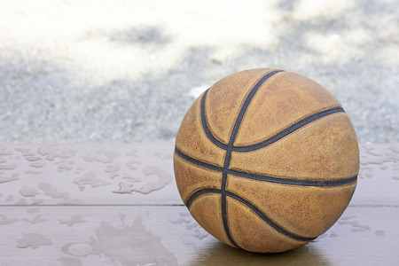 Basketball leather on the wooden chair with water droplets.