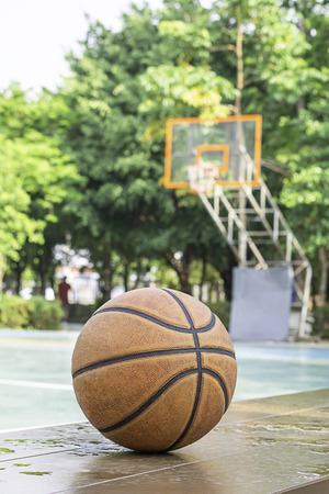 Basketball leather on the wooden chair with water droplets Background basketball court and park.
