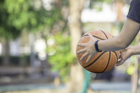 Leather basketball in hand of a woman wearing a watch Background blur tree in park. Standard-Bild