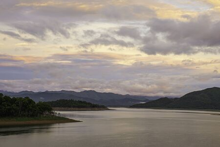 The reflection of the Sun and the clouds on the sky Background mountain and water at Kaeng Krachan dam in phetchaburi , Thailand. Stock Photo