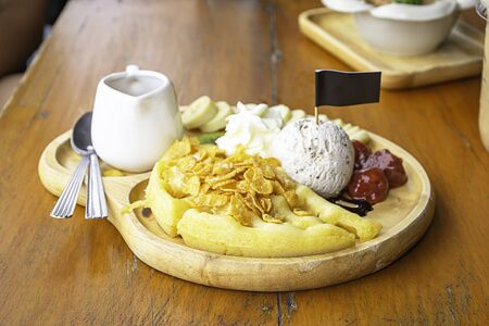 Sweet water pour on the waffle with ice cream and fruits including bananas, kiwi and strawberries in wooden plate on table.