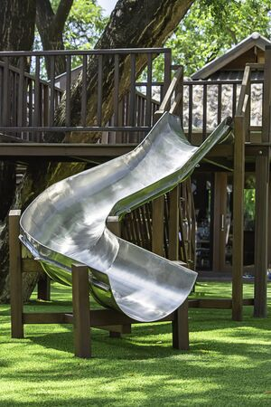 slider made of stainless steel and the structure is made of hardwood On the lawn.