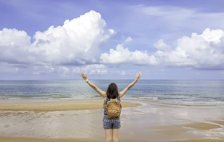 Women raise their arms and shoulder backpack on the beach  background sea and sky at Chanthaburi in Thailand.
