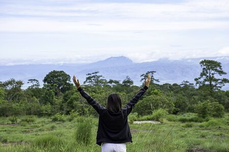 Women raise their arms looked at the mountains and trees at Phu Hin Rong Kla National Park , Phetchabun in Thailand. Stock Photo