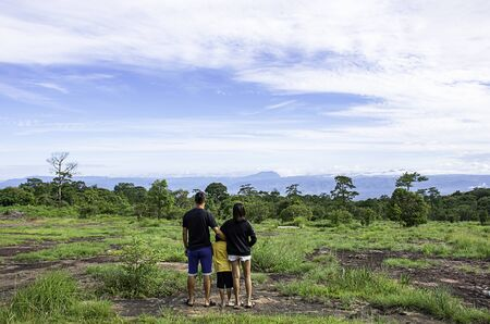 Father and mother hugged their son and looked at the mountains and trees at Phu Hin Rong Kla National Park , Phetchabun in Thailand.