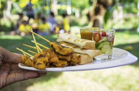 Pork Satay with coconut milk and bread with peanut dipping sauce on white plastic plate in hand.